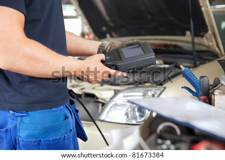 Mid section of mechanic holding a diagnostic tool - stock photo