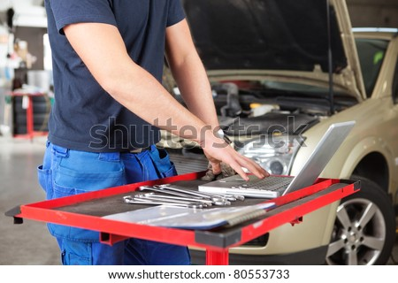 Mid section of mechanic working on laptop in a garage - stock photo