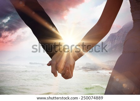 Mid section of newlywed couple holding hands in park against sunrise over magical sea - stock photo