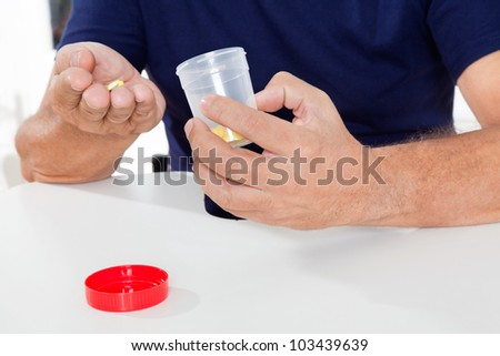 Mid section of senior man holding pills and bottle