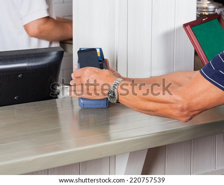 Mid section of senior man paying through smartphone at cash counter - stock photo