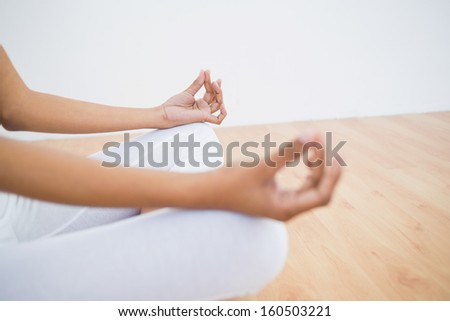 Mid section of slender young woman meditating sitting in lotus position