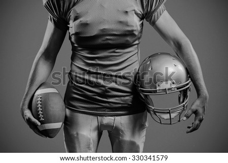 Mid section of sportsman holding American football and helmet against red background