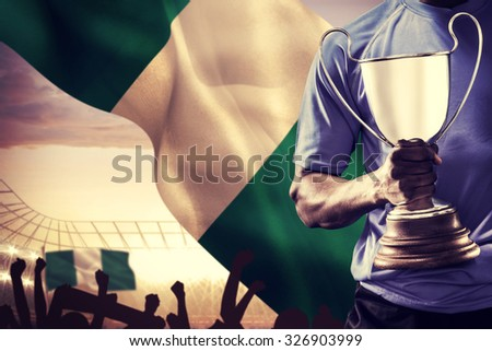 Mid section of sportsman holding trophy and rugby ball against large football stadium under cloudy blue sky - stock photo