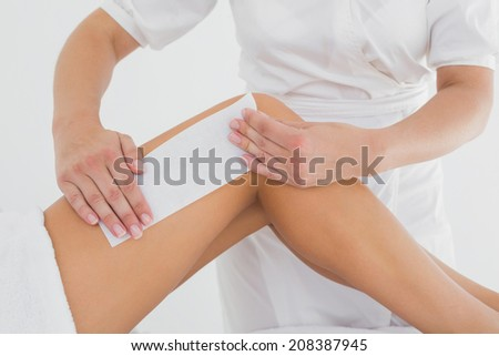 Mid section of therapist waxing woman's leg at spa center - stock photo