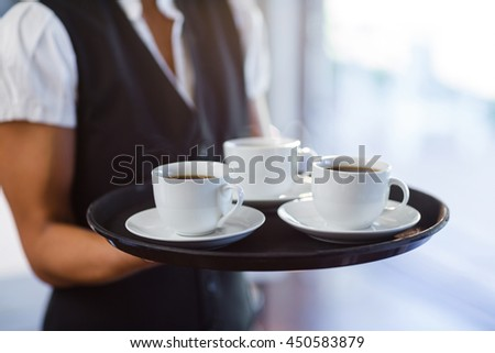 Mid section of waitress holding a tray of coffee cups in restaurant