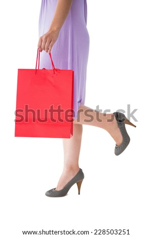 Mid section of woman holding red shopping bag on white background