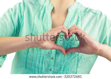 Mid section of woman making heart shape of fingers against white background - stock photo