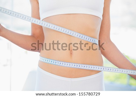 Mid section of woman measuring her waist in bright fitness studio