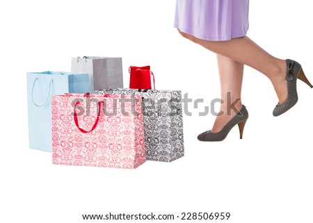 Mid section of woman with shopping bags on white background