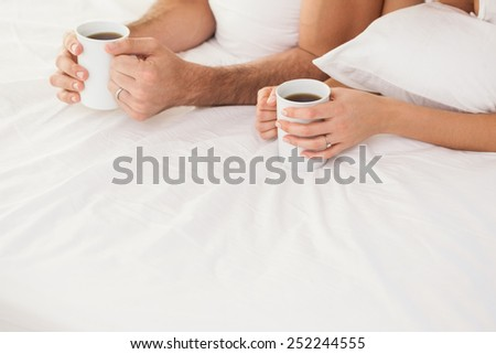 Mid section of young couple having coffee in bed at home in bedroom - stock photo