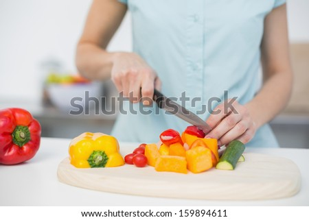 Mid section of young slender woman cutting vegetables standing in kitchen