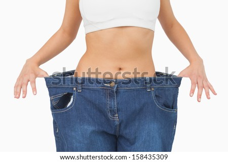 Mid section of young slim woman wearing too big jeans on white screen - stock photo