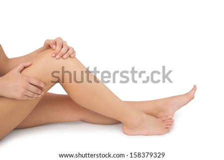 Mid section of young woman sitting on floor touching her injured knee on white background