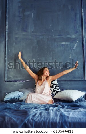 Mid shot of a cheerful girl stretching in bed while looking at the window. Tanned slim woman waking up and stretching