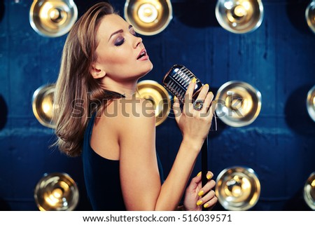 Mid side shot of a classy woman singing in studio with a retro silver microphone on spotlights blurred background