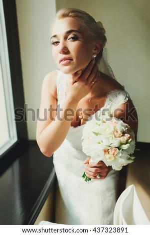 Midday sun illuminates pretty bride's face - stock photo