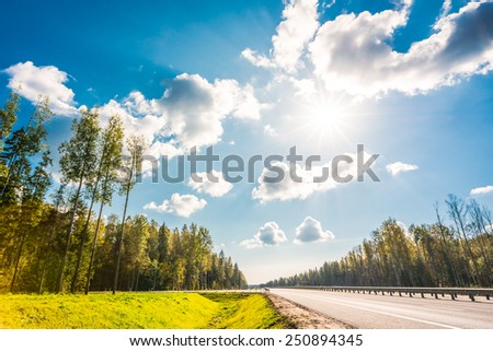 Midday sun on country roads in the forest - stock photo