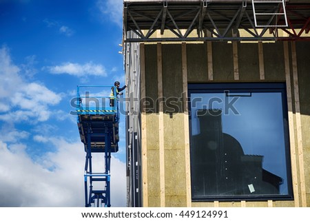 MIDDELFART, DENMARK - JULY 7, 2016: Workers installing windows on the new town hall in Middelfart, July 7, 2016, Denmark - stock photo