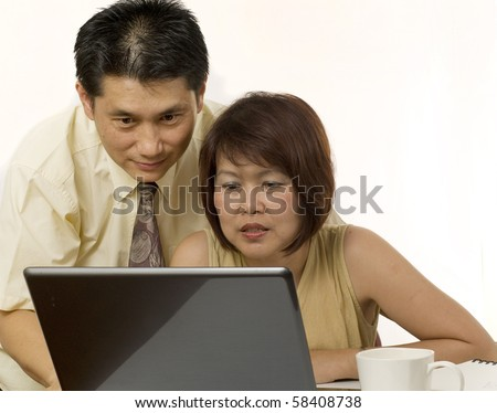 Middle age Asian couple using computer for internet