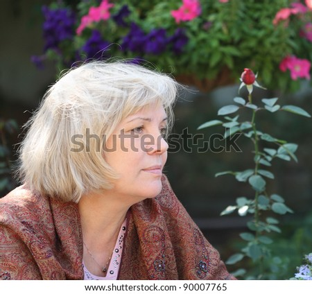 Middle age blonde woman in the beautiful garden - stock photo
