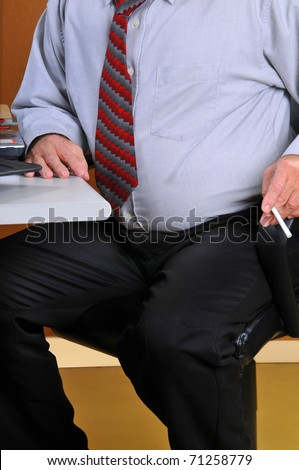 Middle age business man sitting at his desk preparing to leave for a cigarette break. His heavy stomach suggests he is sedentary and needs to exercise and stop smoking. - stock photo