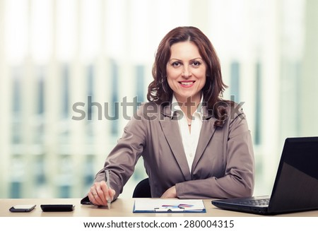 Middle-age business woman working in office. Portrait of smiling business woman. Toned photo - stock photo
