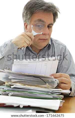 Middle age businessman looking at document through magnifying glass