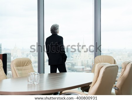 Middle age businessman looking out the window at the panorama of the city - stock photo