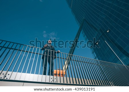 Middle-age contemporary businessman leaning on a handrail holding smart phone - work, business, conversation concept - stock photo