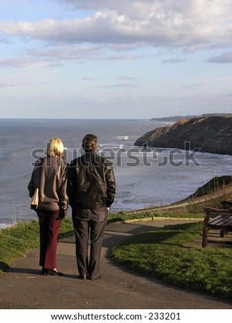 Middle age couple enjoy the views on Scarborough coastline. - stock photo