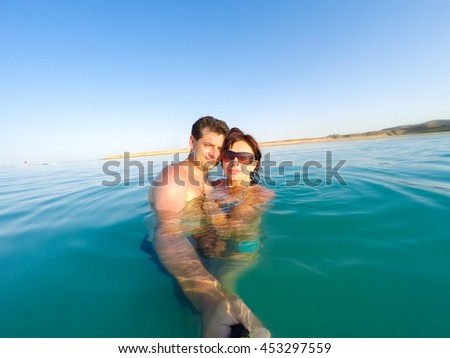 Middle age couple having fun in the water summertime holidays in Egypt. Couple in love shooting selfie photo. Woman with sunglasses