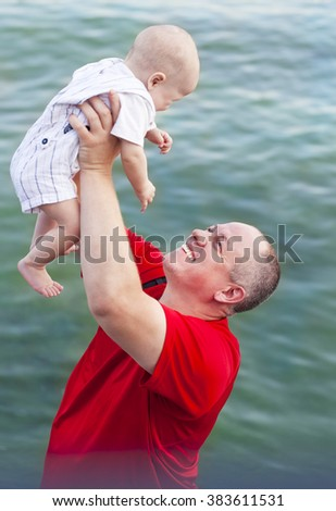 Middle age father and his little son walking along the river - stock photo