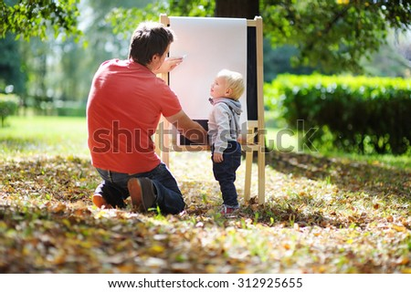 Middle age father and his toddler son drawing  - stock photo