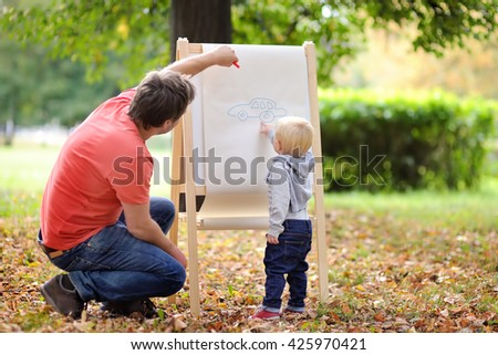Middle age father and his toddler son drawing car