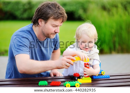 Middle age father with his toddler son playing with colorful plastic blocks  - stock photo