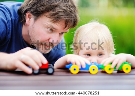 Middle age father with his toddler son playing with toy trains outdoors