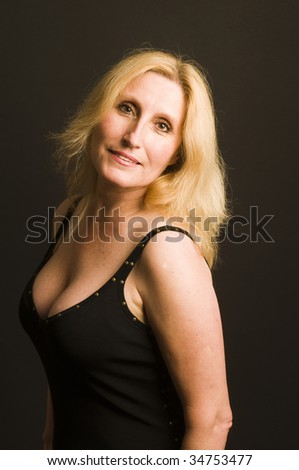 middle age glamorous blond woman posing in low cut little black cocktail dress in photo studio - stock photo