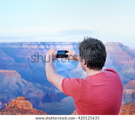 Middle age male tourist making mobile photo of the famous Grand Canyon from Mather Point - stock photo