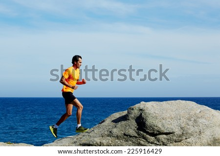 Middle age man at workout outdoors jogging along the sea at sunny day, male jogger in fluorescent t-shirt runs over sea rocks at morning training outdoors - stock photo