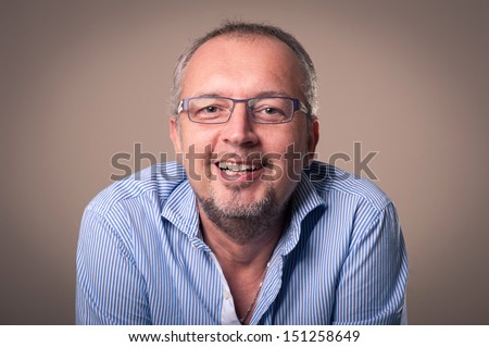 Middle age man close up portrait against dark background. - stock photo