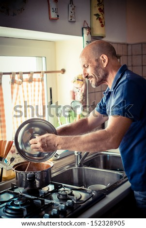 middle age man cooking  at home
