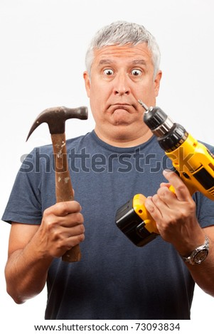 Middle age man holding a hammer and power tool with a dumbfounded confused expression. - stock photo