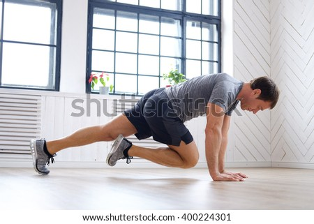 Middle age man in a grey t shirt doing abs workouts on the floor. - stock photo