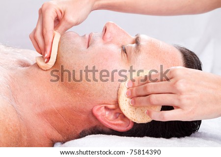 middle age man receiving facial massage in beauty spa - stock photo