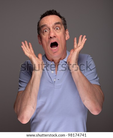 Middle Age Man Screaming in Shock with Hands Raised on Grey Background