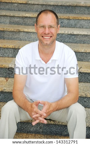 Middle age man sitting on the steps - stock photo