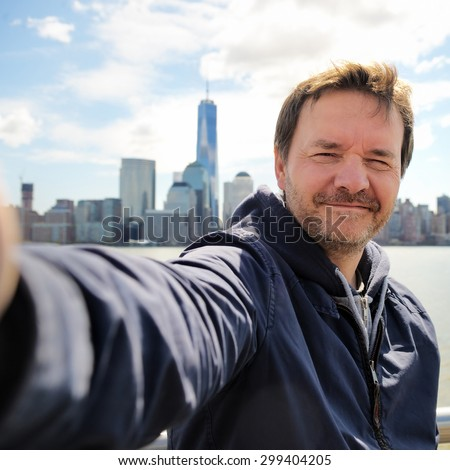 Middle age man taking a self portrait (selfie) with Manhattan skyscrapers in New York City - stock photo