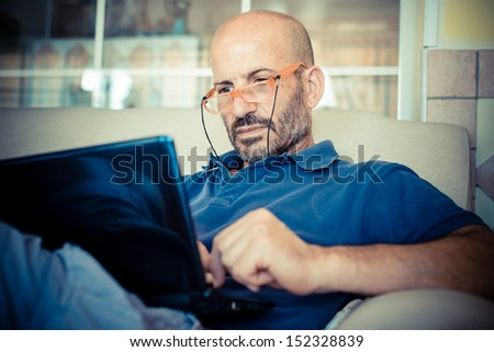 middle age man using notebook at home - stock photo