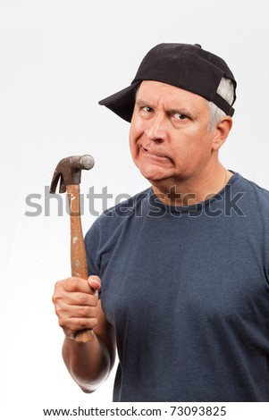 Middle age man wearing a baseball cap holding a hammer with a angry frustrated expression. - stock photo